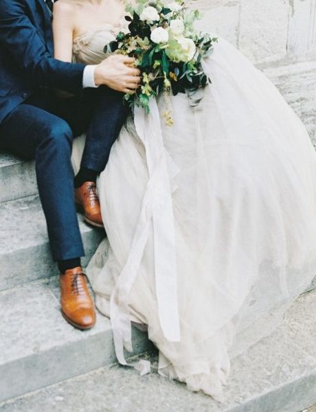 Bride and groom sitting on steps holding flowers