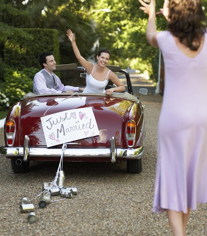 Groom With Bride In Car Throwing Bouquet Towards Wedding Planner