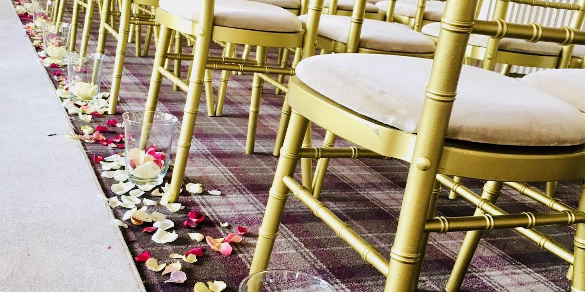 Gold Chiavari Chairs with fresh rose petals and candles